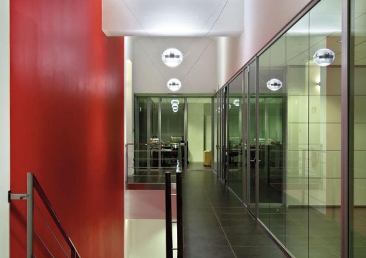 Lungo corridoio con rampa di scale in primo piano sulla sinistra, appoggiate su parete di color rosso cremisi. Sulla destra parete vetrata divisoria molto regolare che prosegue fino in fondo.